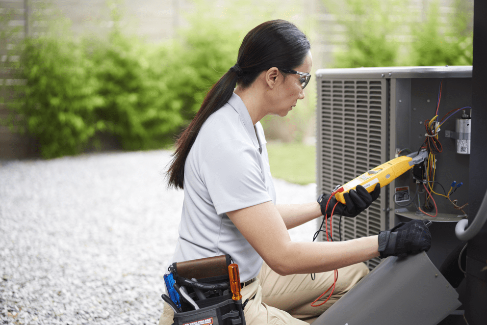 A technician checking the electrical wires of an AC unit